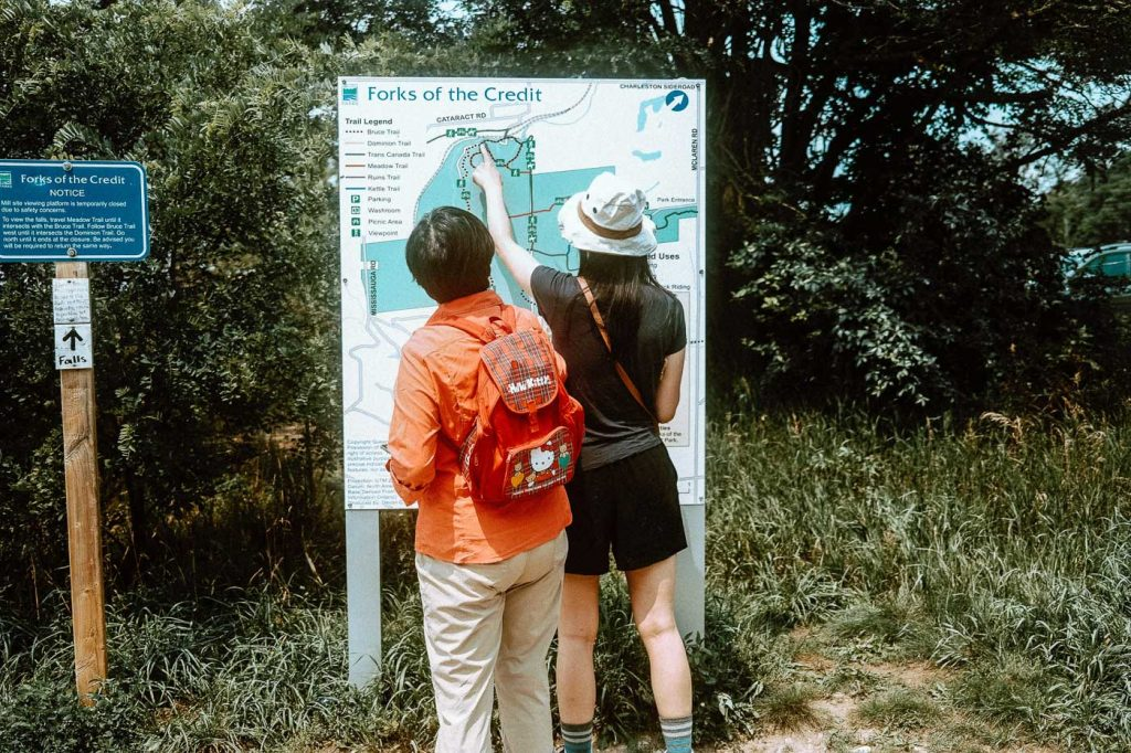 Two women examining Park Map at Forks of the Credit Provincial Park, Caledon, Ontario