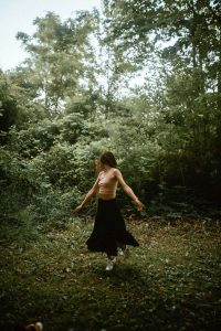 Woman spinning in a clearing at McCormick Trail located in Hamilton, Ontario