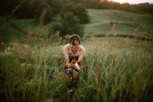 Woman smiling while crouched in meadow petting a corgi that is facing her. Location: McCormack Trail located in Hamilton, Ontario