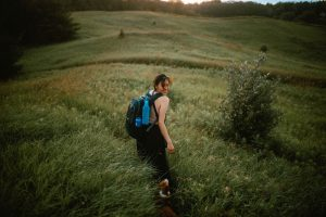 Woman wearing backpack in a field turning around to smile. Location: McCormack Trail located in Hamilton, Ontario
