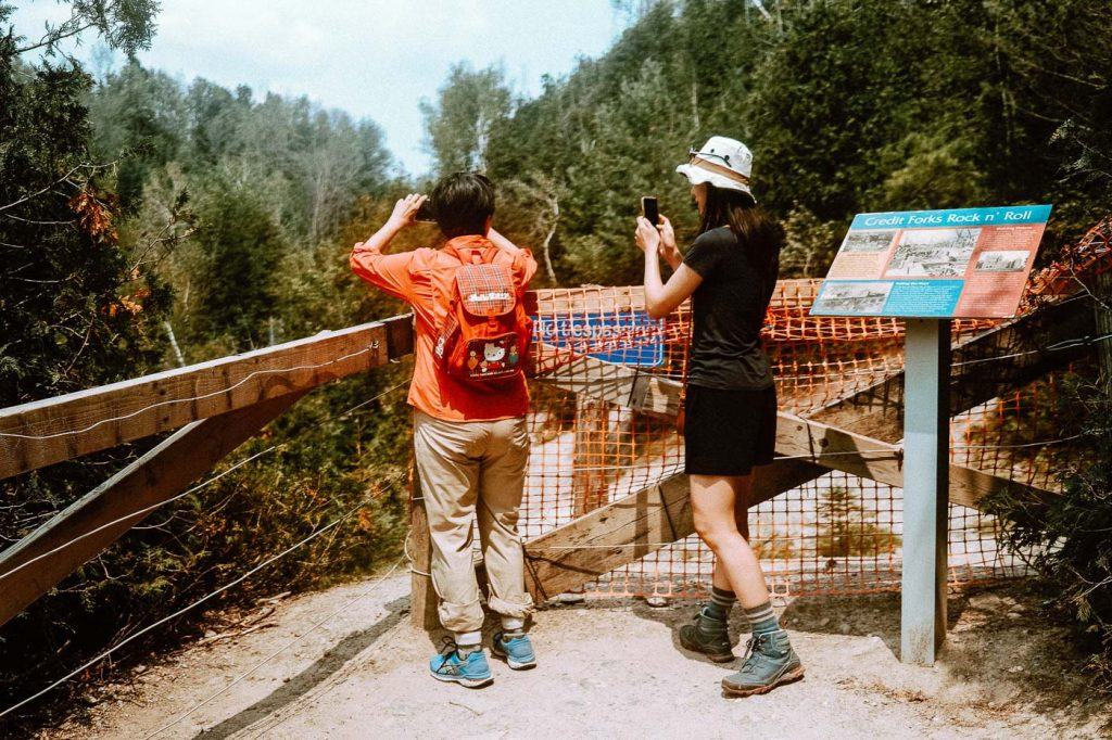 Two women standing at the fenced off lookout point for the Cataract Falls at Forks of the Credit Provincial Park