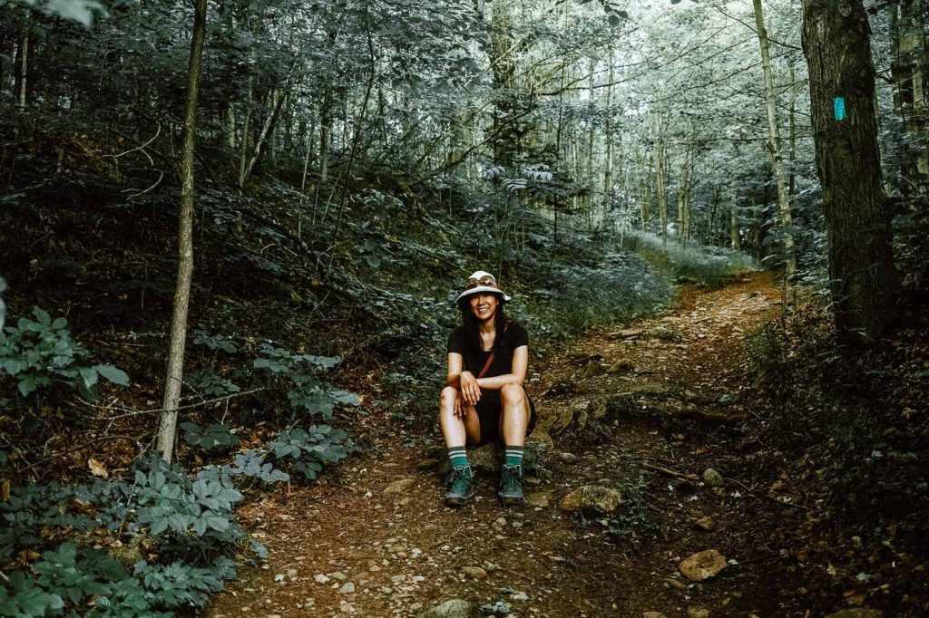 Woman sitting in the middle of the trail - taking a break after climbing the Dorothy Medhurst Sidetrail at Forks of the Credit Provincial Park