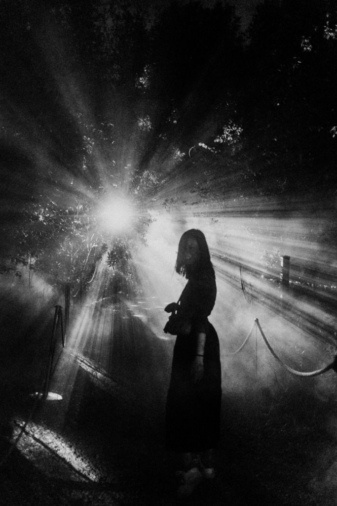 Black and White Silhouette of woman standing in front of a single bright light set behind a forest. Terra Lumina at the Toronto Zoo