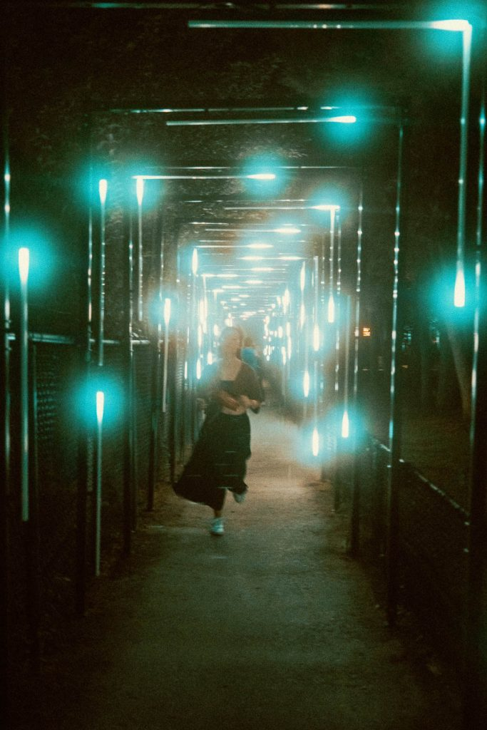 Woman running towards camera while staggered light arches frames the picture at the Terra Lumina event at the Toronto Zoo