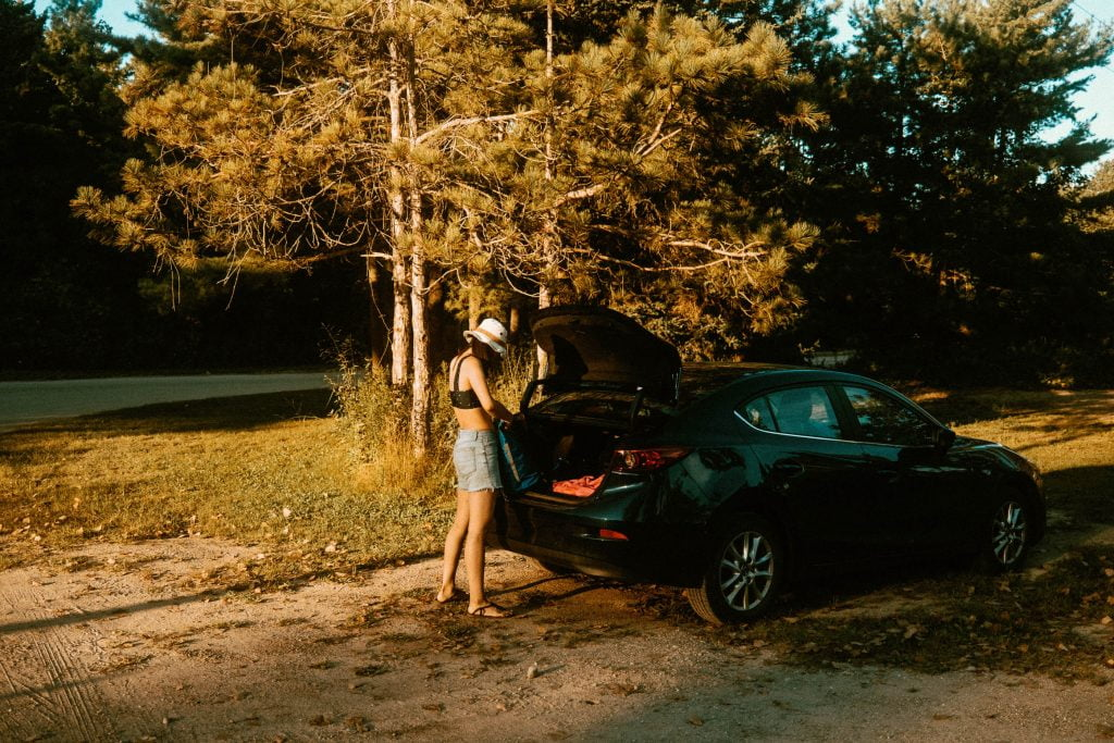 Woman packing items into a trunk of a car parked at Long Point Provincial Park's West End - near the dog beach access area