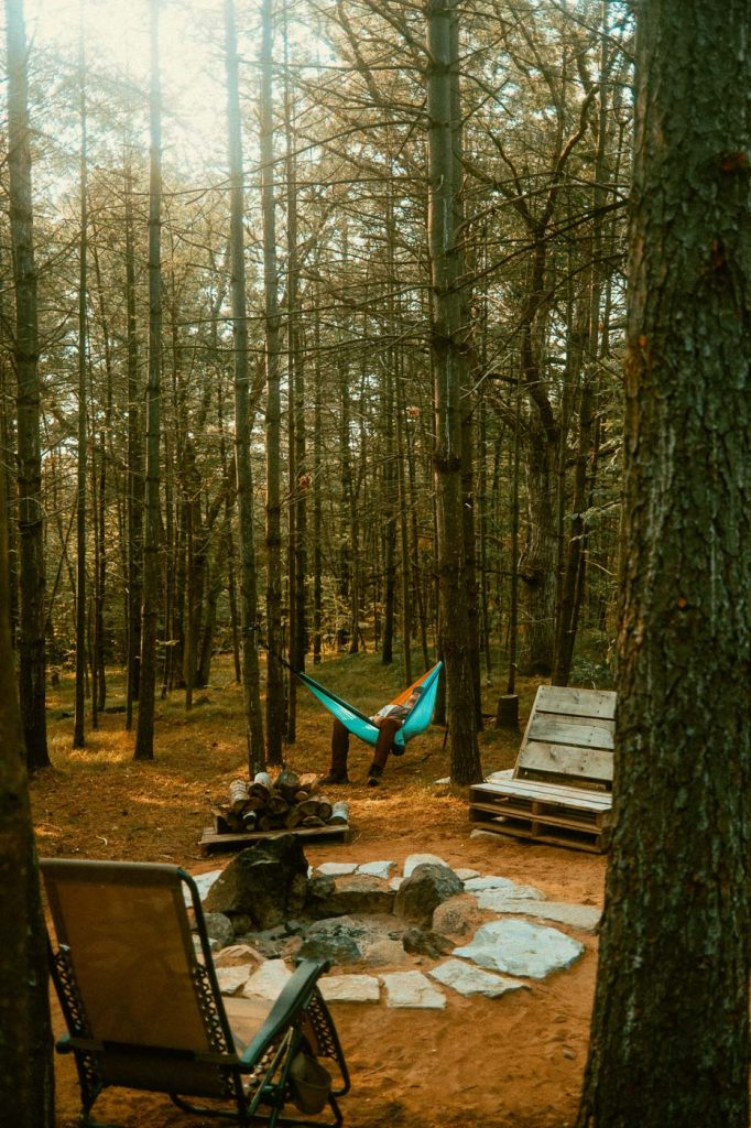 Relaxing on a hammock by a firepit at Sibo's Bell Tent Glamping Site in Verona, Ontario