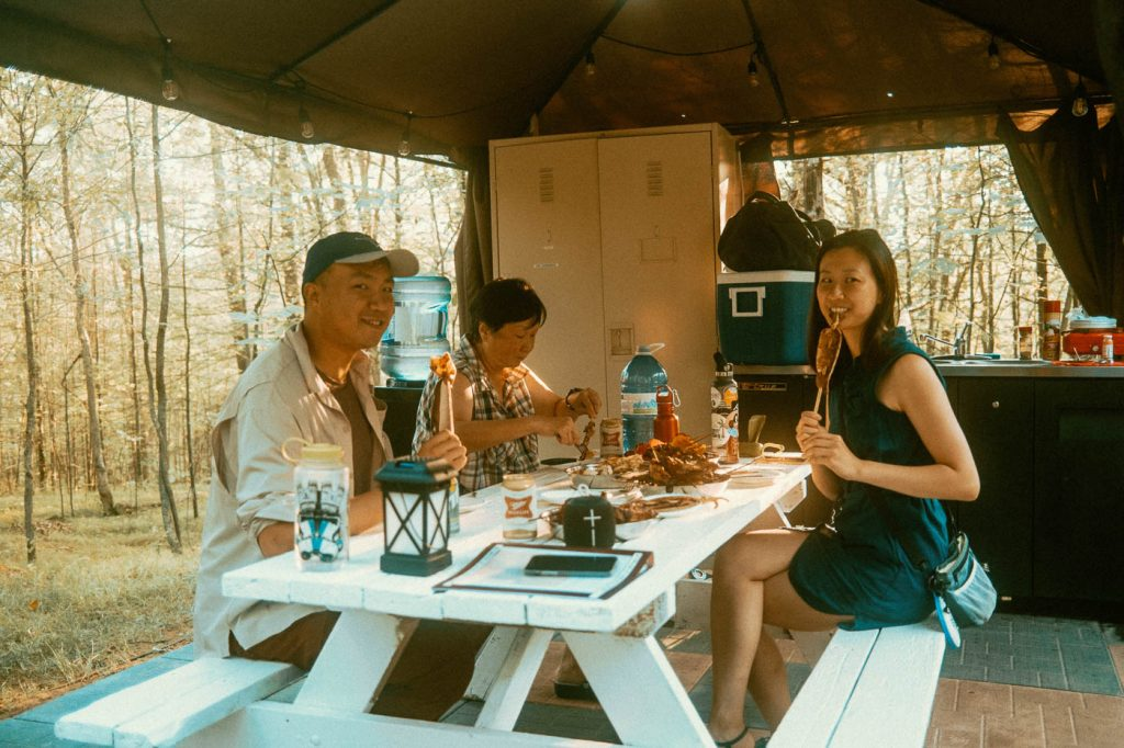 Family Dinner inside the sheltered kitchen in Sibo's Bell Tent Glamping Site in Verona, Ontario