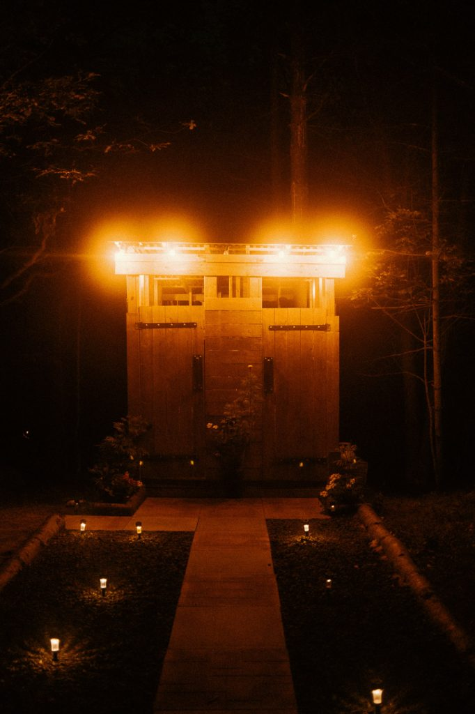 Shower and Toilet Cabin Lit Up at night on Sibo's Bell Tent Glamping Site in Verona, Ontario