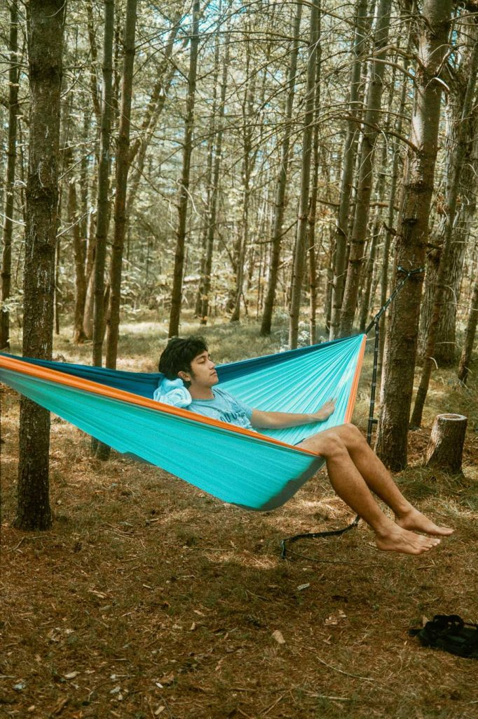Relaxing on a hammock on Sibo's Bell Tent Glamping Site in Verona, Ontario