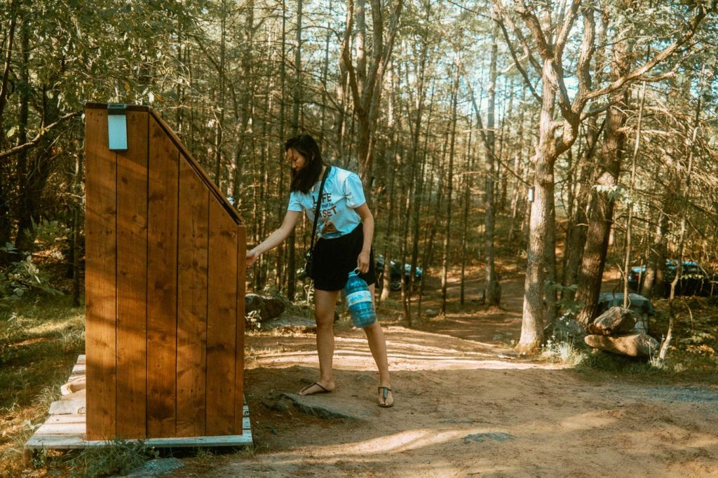 Maria recycling a water bottle at the onsite dumpster/recycle/cleaning station on Sibo's Bell Tent Glamping Site in Verona, Ontario