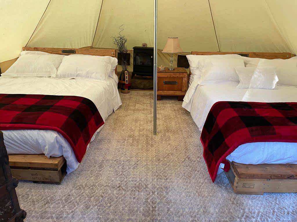 Interior of Sibo's Bell Tent in Verona, Ontario with two double beds, a heater, a bedside table and lamp
